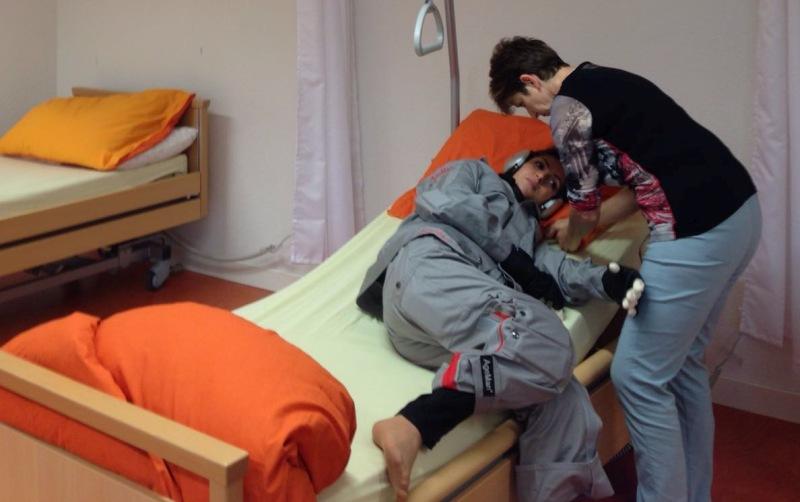 Fortbildung Altenpflege mit dem Alterssimulationsanzug AgeMan. Junge Frau im Pflegebett wird von Kollegin gelagert.